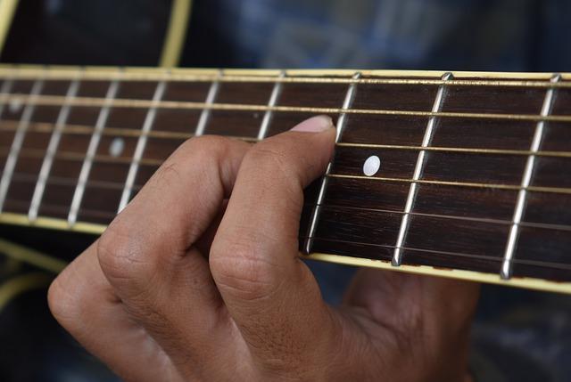 יד לוחצת על גיטרה